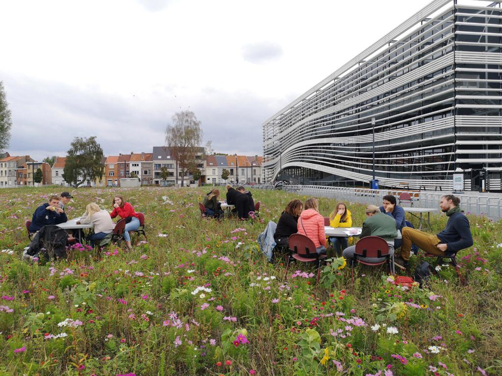 mensen die brainstormen aan tafels tussen de bloemen voor campus Schoonmeersen gebouw T