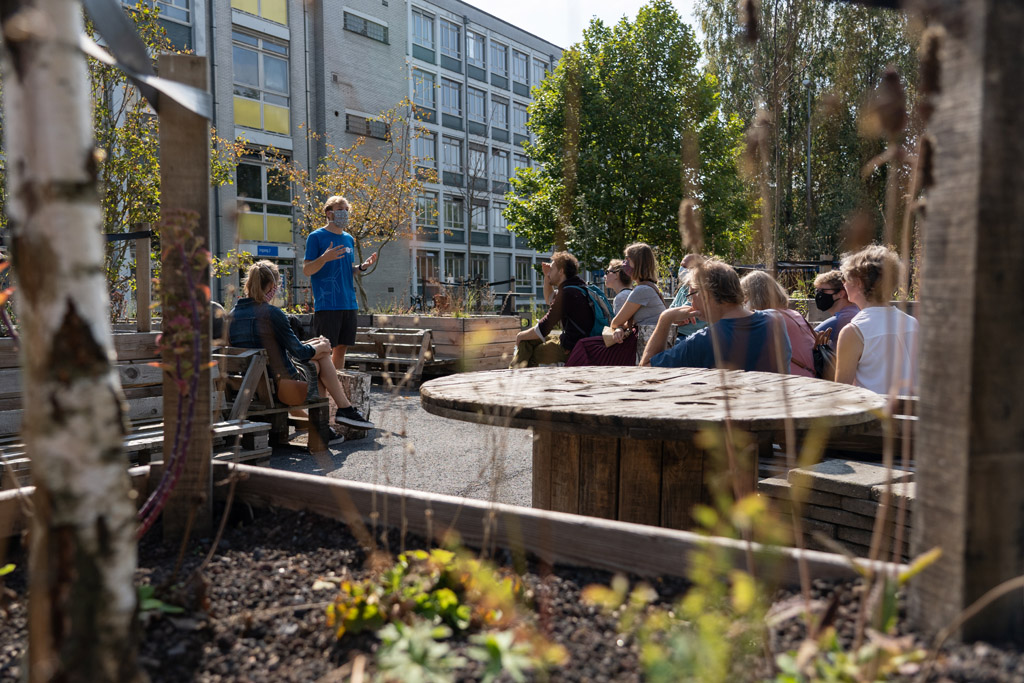 zittende mensen op houten meubelen die luisteren naar een rechtstaande man die uitleg geeft op het studentenplein aan campus Schoonmeersen gebouw B
